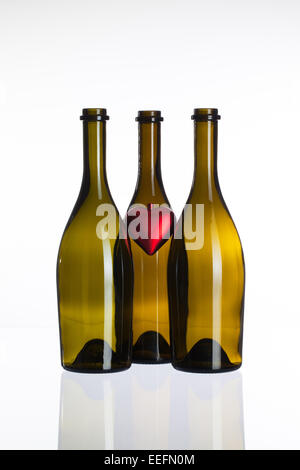 Empty bottles of wine and red heart on a glass table - Stock Photo