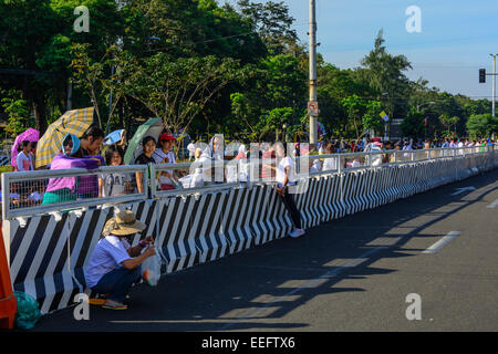 Intramuros, Manila, Philippines, 16th Jan 2015. Filipinos from all walks of life gather and wait in one of the streets - Stock Photo