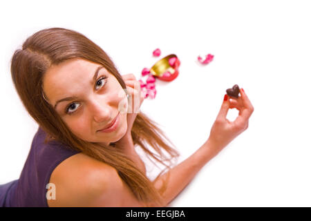 Young girl holding a chocolate heart on a white background, isolated - Stock Photo