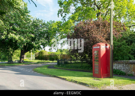 A traditional red telephone box in an English village. - Stock Photo