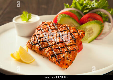 Grilled fish tikka served on a plate with salad and tarter sauce dip and salad with lemon, on a dark wood background - Stock Photo