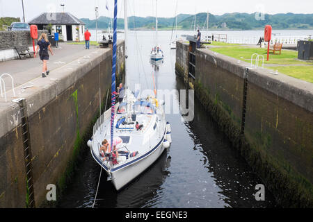 A yacht entering the first lock at Crinan on the Crinan Canal in Scotland. - Stock Photo
