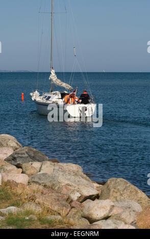 Sailing boat passing buoy outside Norsminde Harbour, Denmark - Stock Photo