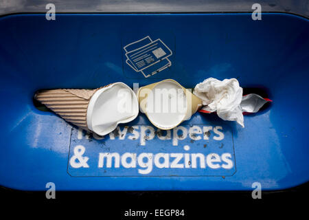 Instead of the intended newspapers and magazines, passers-by have instead stuffed coffee cups and general paper - Stock Photo
