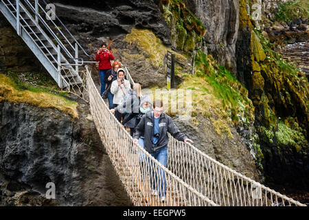 People  crossing Carrick-a-Rede rope bridge - Stock Photo