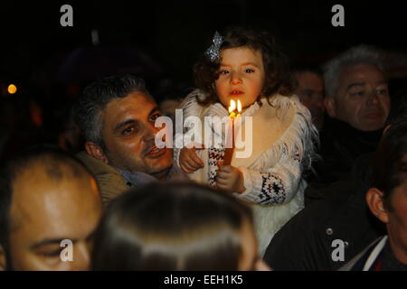 Athens, Greece. 18th January 2015. A father holds his little daughter in his arms. She carries some candles. The - Stock Photo