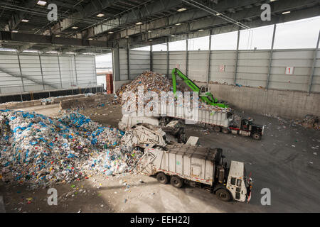 Garbage trucks dump trash in the tipping area from the city's curbside recycling program at the Sims Municipal Recycling - Stock Photo