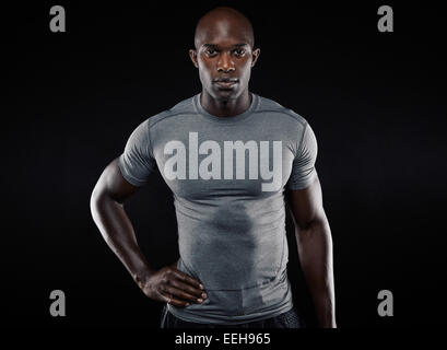 Portrait of muscular young man in sportswear looking at camera against black background. Strong African athlete - Stock Photo