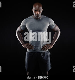 Portrait of muscular young man in sportswear standing with his hands on hips against black background. Strong African - Stock Photo