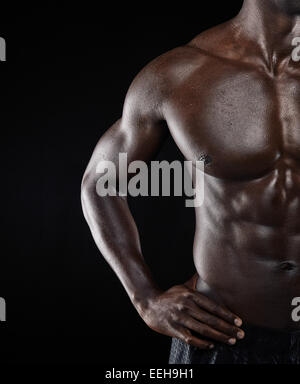 Close-up shot of young African muscular man body against black background. Shirtless male model with muscular build. - Stock Photo