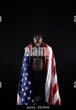 Shirtless muscular man with American flag on black background. Olympics athlete with USA flag looking down. - Stock Photo