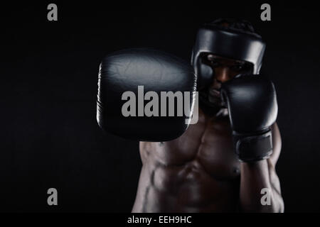 Young muscular man practicing boxing. African male throwing punch towards camera against black background. Fit young - Stock Photo