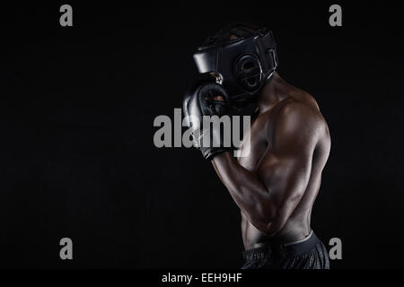 Side view of a young male boxer in a fighting stance on black background. African male boxer blocking his face with - Stock Photo