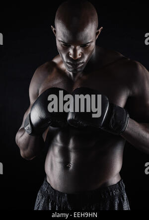 Fit young man wearing boxing gloves on black background. Professional boxer preparing for fight. - Stock Photo