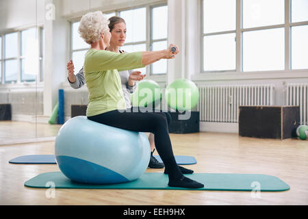 Female trainer assisting senior woman lifting weights in gym. Senior woman sitting on pilates ball doing weight exercise.