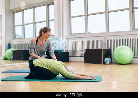 Female trainer helping senior woman doing yoga. Elder woman bending over a exercise mat with personal instructor - Stock Photo