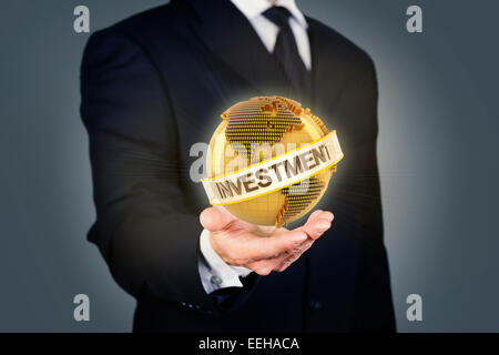 Businessman holding a golden globe with investment text - Stock Photo