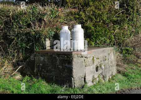 Old milk churns on a milk churn stand at a farm entrance Pembrokeshire Wales Cymru UK GB - Stock Photo