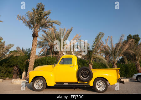 Classic yellow Chevy pickup truck under the palm trees - Stock Photo