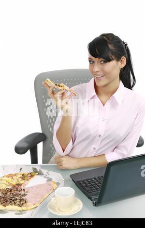 Junge Frau isst Pizza im Buero, Businesswoman eating pizza in the office (Modellfreigabe) - Stock Photo