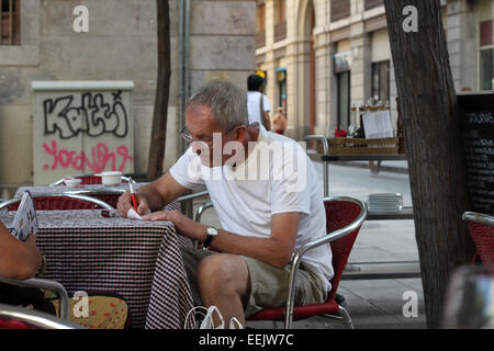 Tourist checking the bill, sitting at table of outdoor café in El Raval in the centre of Barcelona - Stock Photo