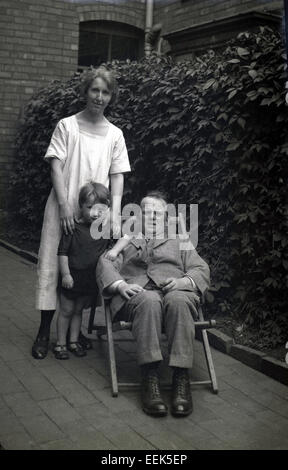 1920s historical picture of a man sitting in a deckchair, and mother and young boy standing beside him in side passage - Stock Photo
