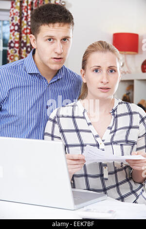 Worried Couple Discussing Domestic Finances At Home - Stock Photo