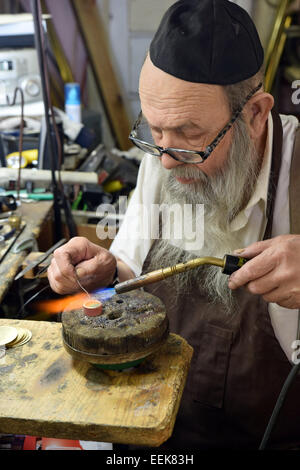 Portrait of religious Jewish silversmith & metalworker in his studio soldering while making a ring. In Brooklyn, - Stock Photo