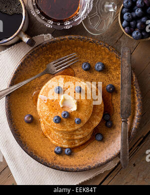 Pancakes with blueberries and maple syrup on a rustic tabletop. - Stock Photo