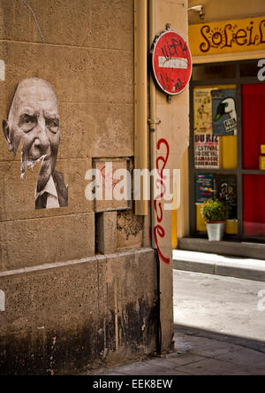French ripped paper posters of mans face on wall, shadows and sunlight no entry traffic sign - Stock Photo