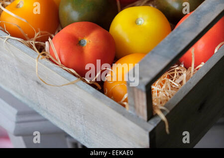 colourful tomatoes in wooden box - Stock Photo