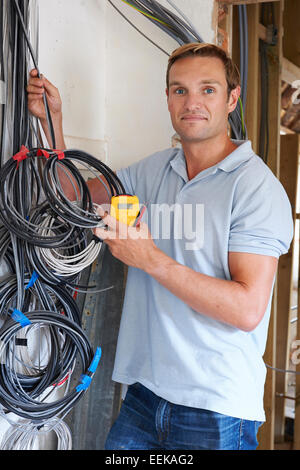 Electrician Fitting Wiring On Construction Site - Stock Photo