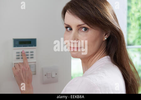 Woman Setting Control Panel On Home Security System - Stock Photo