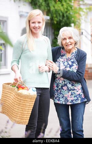 Teenage Girl Helping Senior Woman To Carry Shopping - Stock Photo