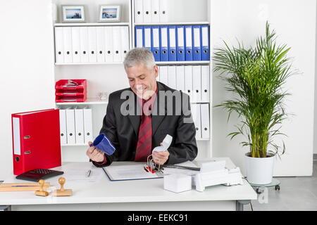 Mann mittleren Alters sitzt im Büro am Schreibtisch mit leerer Tasse Kaffee in der Hand, Middle-aged man sits in - Stock Photo