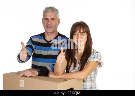 Paar mittleren Alters mit Umzugskartons, hält die daumen hoch, Middle-aged couple with removal boxes, holding up - Stock Photo