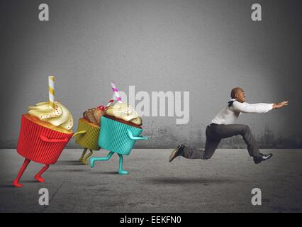Man runs away from sweets and calories - Stock Photo