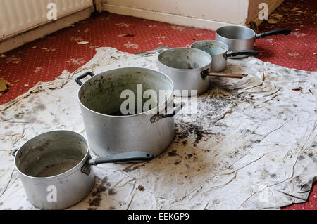 Pots lined up on a carpet to catch water from a leaking ceiling - Stock Photo