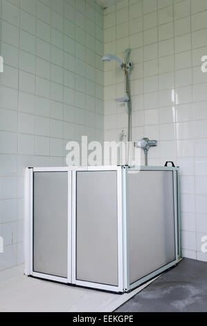 disabled shower in wet room with hand rails and seat in up position