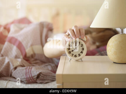 girl turns off the alarm clock waking up in the morning from a call - Stock Photo