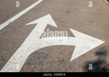 Directional arrows painted on an asphalt road. - Stock Photo