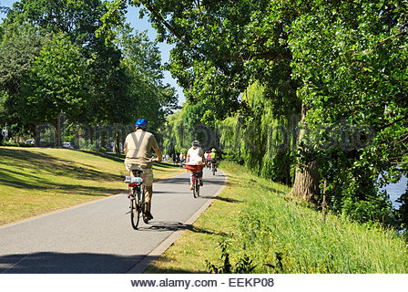 People ride bicycles on a path that runs around the Münstersche Aasee in Münster, Nordrhein-Westfalen, Germany. - Stock Photo