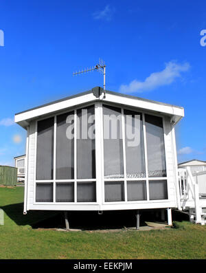 Exterior of a modern white caravan on a park in summer. - Stock Photo