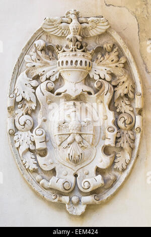 Emblem with royal symbols in bas-relief on a wall - Stock Photo