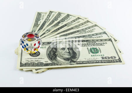 Transparent dice over a series of dollar bills as a concept of gambling with money and engaging in high risk investments - Stock Photo