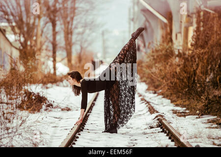 Dancer striking a pose on railway tracks in winter - Stock Photo