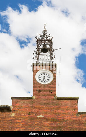 Brick church tower with clock and bell attached to an iron frame - Stock Photo