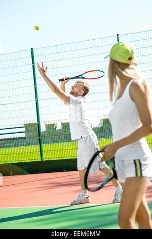 Young married couple playing tennis in white sportwear on the tennis court outside in the summer - Stock Photo