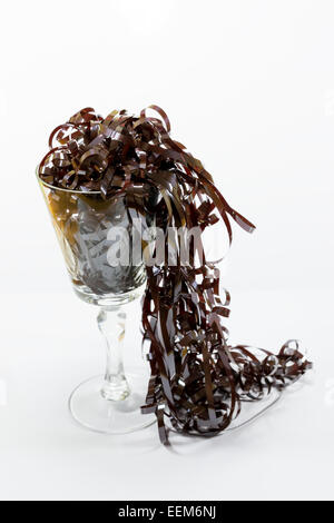 Crystal glass filled with overflowing tangled audio magnetic tape, on white background - Stock Photo