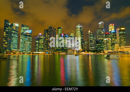 Singapore, Waterfront skyline with illuminated skyscrapers seen from harbor - Stock Photo